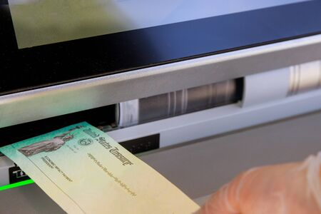 Hand of a woman with deposit stimulus check in banking using an ATM Standard-Bild