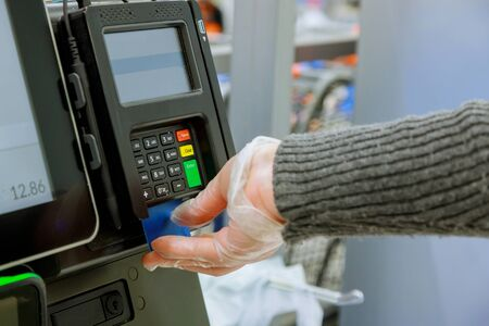 Credit card payment terminal in shop on human hand in gloves respecting health standards during the pandemic of Coronavirus COVID-19