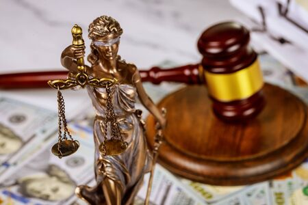 Judge's gavel with books and statue of Justice scales on law office working law document