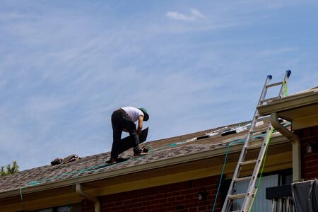 Roof repair, worker with replacing gray tiles shingles on house being applied Stok Fotoğraf