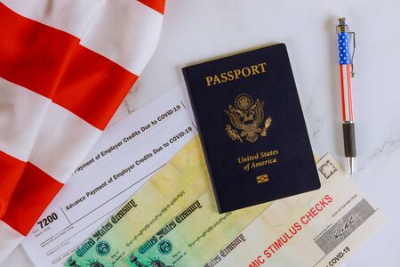 Stimulus relief check on Passport of USA on American flag About Form 7200, Advance Payment of Employer Credits Due to COVID-19 Standard-Bild