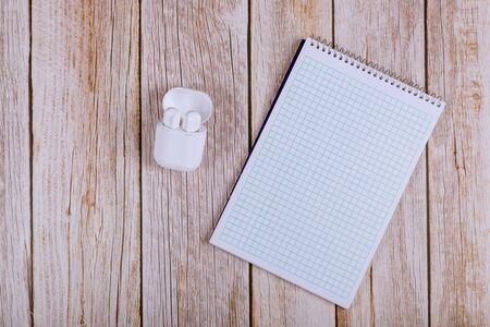 Open notebook with wireless headphones on workplace wooden desk