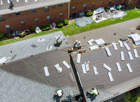 A worker replace shingles on repairing the roof of a home a renovation roof covering Standard-Bild