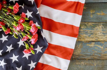American flag on Memorial day honor respect patriotic military US in pink carnation old wooden background
