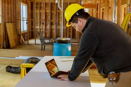 Inspector with yellow hard hat and tape measure and tablet PC at work construction site