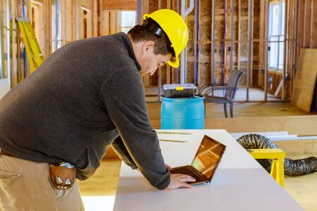 Inspector in new construction house with tablet making notes reviews documents.