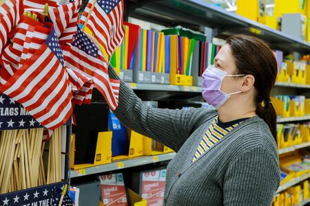 Young woman chooses us flag onmemorial day in store in masks, american holidays