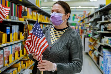 American flags on sale a store on memorial day celebration, women in masks buying a US flags, american holidays