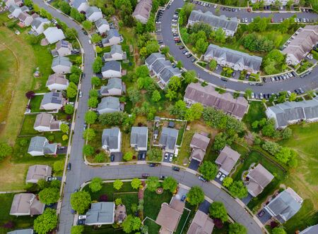 View of winding streets and roads in a residential area small town neighborhood with landscape roofs of houses