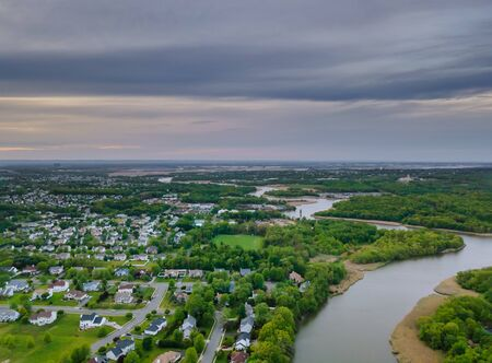 Aerial top view waterfront suburban street of middle class suburban neighborhood with houses