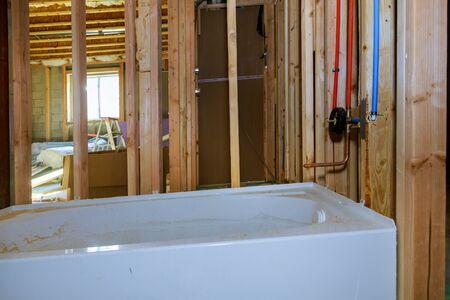 Interior framing of bathroom a new acrylic bathtub with a wood frame installing PVC