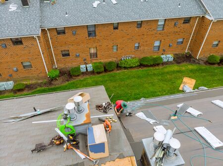 Roofer working on replacement asphalt shingle roof construction