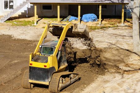 Mini bulldozer landscaping works on construction working with earth while doing scoop excavator Standard-Bild