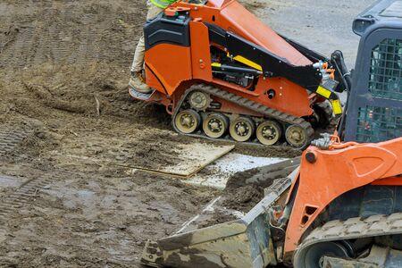 Backhoe digging the ground during works at for soil construction excavation earthmoving Standard-Bild