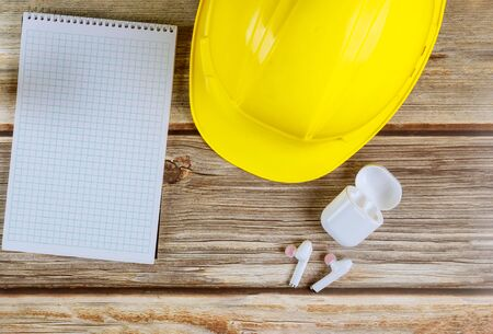 Engineers maintenance office construction, yellow hard hat with notepad wireless headphones on vintage wood board