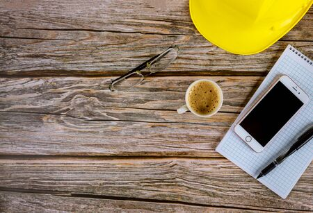 Workspace builders architect office table desk, blank open notebook with pen on yellow hard hat with cup of coffee, smartphone eyeglasses on wooden desk
