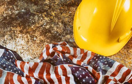 Happy Labor Day USA patriotic, yellow hard hat construction helmet USA flag over wooden deck table background.