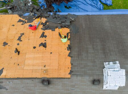 Removal of old roof replacement with new shingles of an apartment building 版權商用圖片