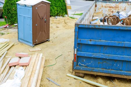 Portable restroom on house under construction in a dumpsters construction garbage new house