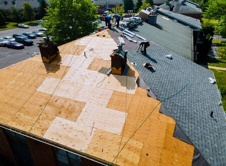 Roof repairs old roof replacement with new shingles of an apartment building Stock Photo