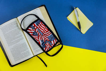 NewYork NY JUNE 11 2020: Holy open Bible with medical mask on the table