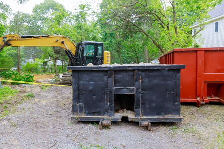 Industrial dumpster filled loaded rubbish removal container renovation building on house under construction Banque d'images