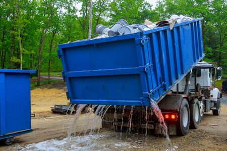Truck loading a full recycling used construction material on the new building work site. Standard-Bild