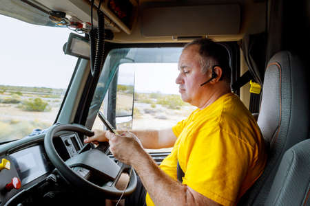 Driver in cabin on highway of smartphone in hand of man sitting behind the wheel of big modern truck vehicle Stock Photo