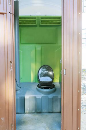 Open portable toilet at construction site for worker in a building