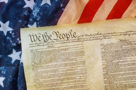 Closeup of a replica of U.S. Constitution document of grunge American flag on We the people Bill of Rights Stock Photo