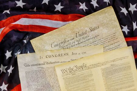 Closeup of a replica of U.S. document of American constitution We the people with USA Flag.