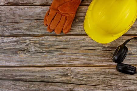 Protective workwear safety standard construction safety earmuffs leather safety helmet protective gloves on wooden table top view