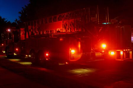 Flashing emergency lights of red fire truck at dusk the city