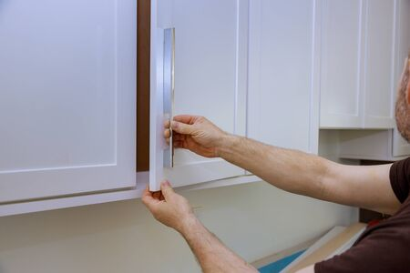 Worker install new handle on the white cabinet assembling of furniture close up