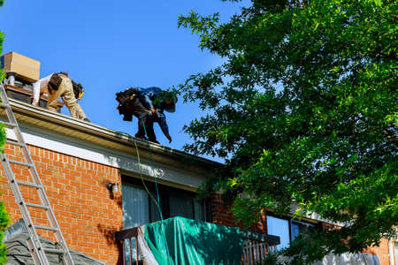 A roofer nailing shingles with air gun, replacing roof cover protection being applied, apartment development