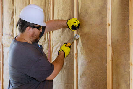 Man installing thermal insulation layer under the wall using mineral wool with fiberglass cold soft focus