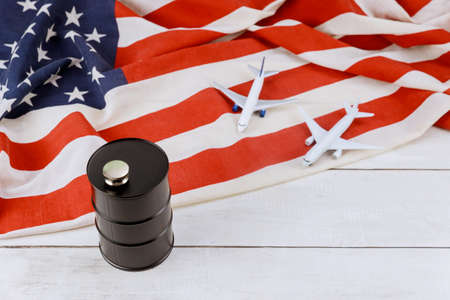 Model airplane on rising world fuel tank oil barrel prices brand USA flag Stok Fotoğraf