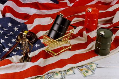 Oil of the black barrel of oil of one hundred US dollar bills on a flag in the USA court showdowns wooden judge hammer Stock Photo