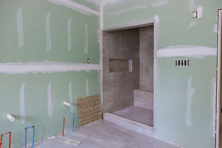 Master Bathroom with new under construction bathroom interior drywall ready for tile in new luxury home