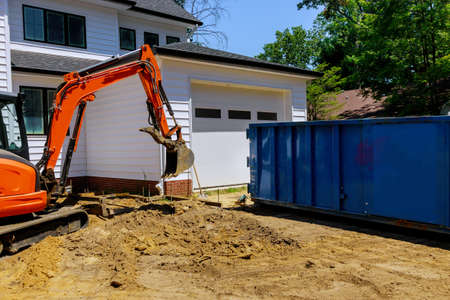 Mini excavator and bobcat on construction site for working in trash container construction dumpsters