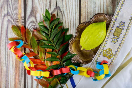 Ritual Jewish festival of Sukkot in the religious symbol Etrog, lulav kippah and tallit praying book
