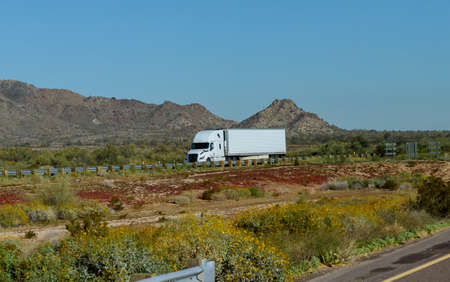 White big rig American long haul semi truck with moving on wide divided turning highway with mountain in USA