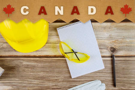 Happy labor day in yellow helmet, national patriotic with Canada on old wooden boards