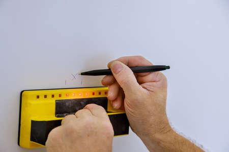 Digital detector man hand is scanning wall by sensors precision stud finder wooden beams Standard-Bild