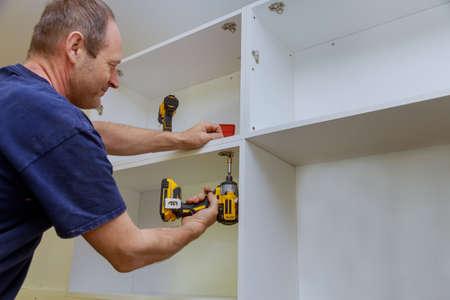 Carpenter installed a kitchen cabinet metal hinges for doors
