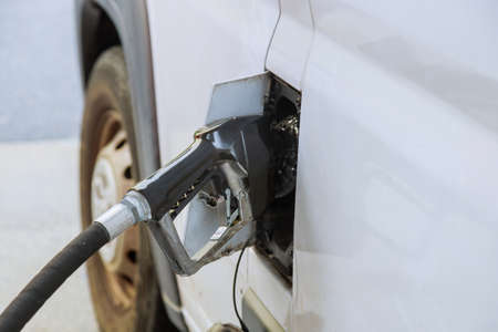 Pumping gasoline car at gas station being filled with fuel on closeup soft focus Stock Photo