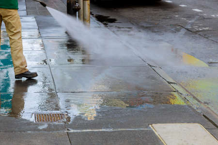 Worker cleaning driveway with high pressure washer splashing the asphalt road border.