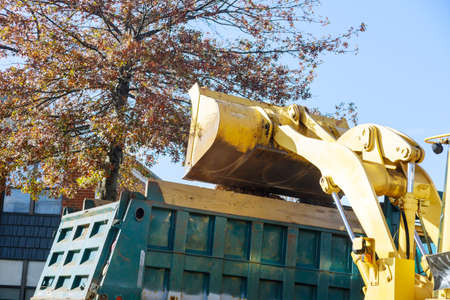 Regular seasonal work on improving the public places city team removes the fallen leaves with an excavator a truck 写真素材