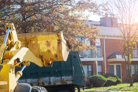 Regular seasonal work on city improvement team removes the fallen leaves with an excavator and a truck improving the public places 写真素材