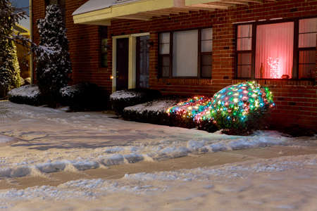 Evening lighted house and road in the snowy residential area and parking lot Stockfoto